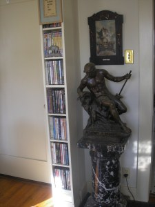 This is on the way to the kitchen but behind that green paisley chair. That statue is inscribed on the side facing the IKEA dvd holders.