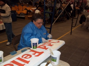Cathy is applying white rice (?) to the Odd Fellows sign. It's cold in the building.