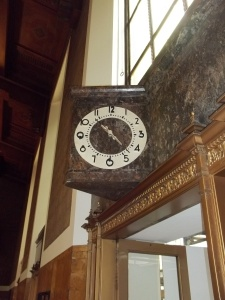This clock is above a doorway that leads to an outside patio.